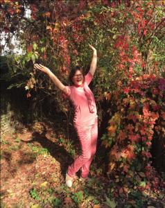 Auf diesem Bild wirft eine in rot gekleidete Frau, im Herbstlaub stehend, voller Freude die Arme hoch mit einem ansteckendem Lächeln im Gesicht.