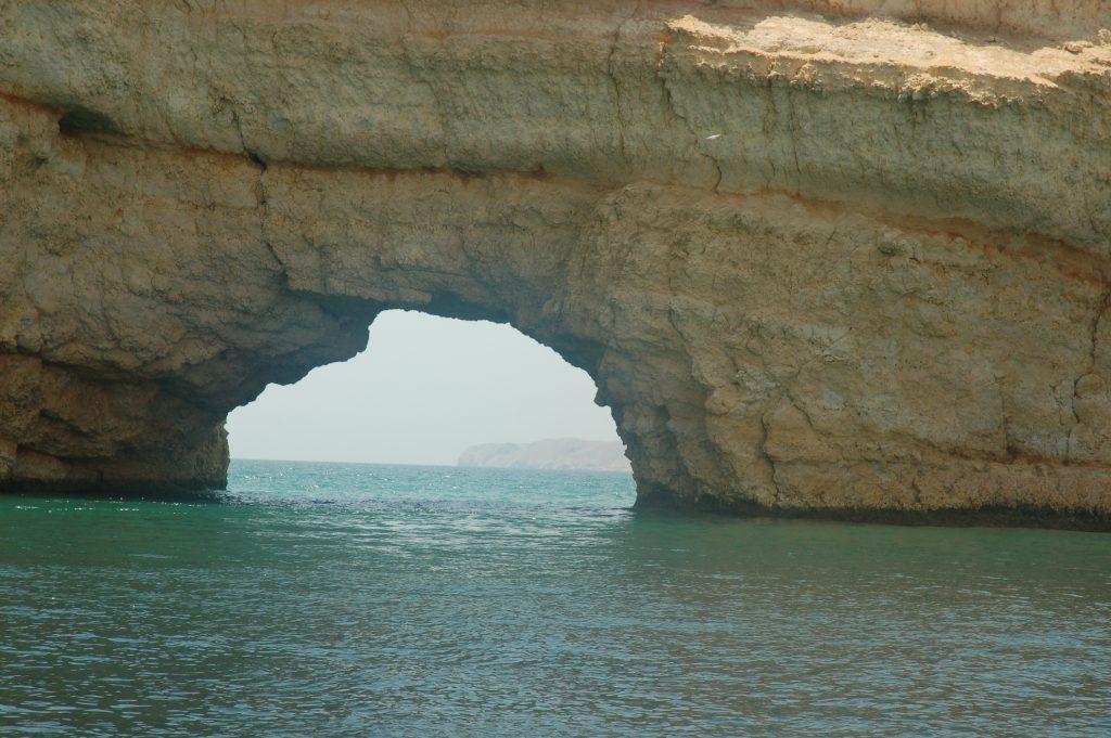 Meer mit einem Felsen, welcher wie ein Tor aussieht.