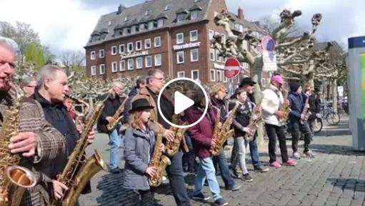 Ein Foto wo viele junge und ältere Saxofon Musiker und Musikerinnen durch die Straßen ziehen