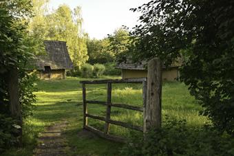 Steinzeitgehöft mit Gartenzaun und Rasen