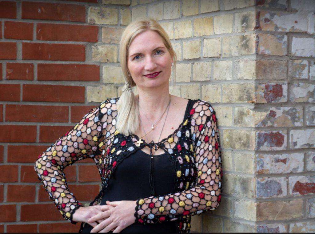 Silvia Erdmann, blone, langhaarige Frau vor Steinwand