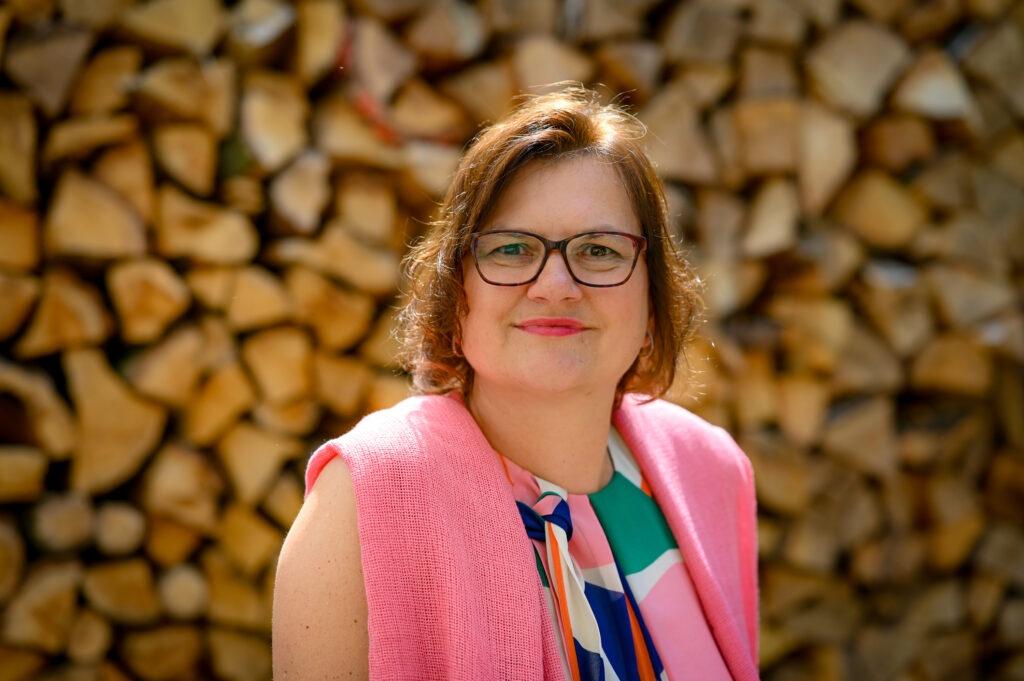 Moderatorin der Gastvortrages vor einem Holzstapel